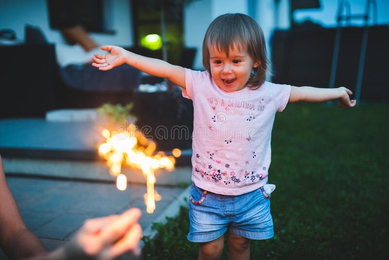 Child seeing sparkler fireworks first time outside stock image