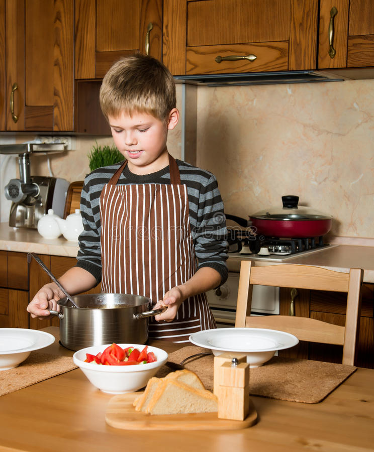 Child serving Borshch, traditional Russian and Ukrainian soup. Pouring soup into a plate with ladle from pan in kitchen. Boy serving Borshch, traditional royalty free stock images