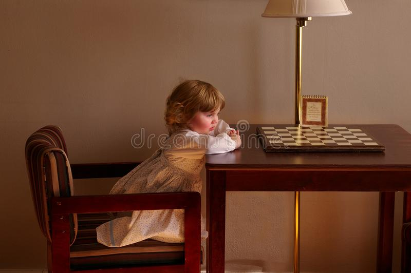 Child Setting on Chair in Front of Table royalty free stock photography