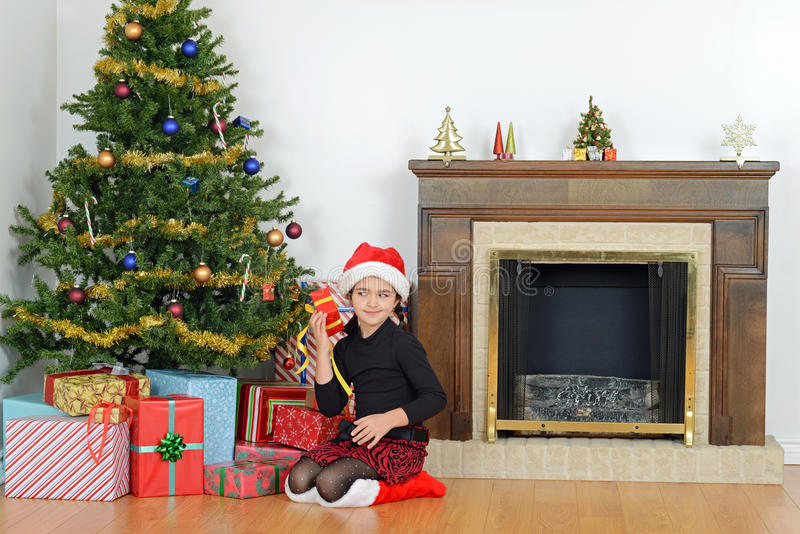 Child shaking christmas present by tree stock image