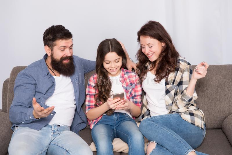 Child share news with mother and father. Little girl child use mobile phone. Happy family at home. Buy online. Child royalty free stock photo