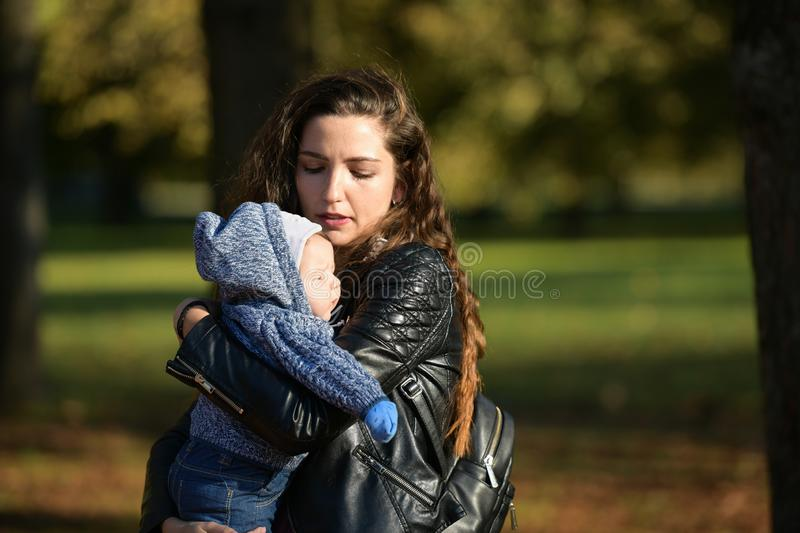 The child shines in the face of the sun. Portrait of a crying girl. The baby is crying. The child holds her ear and cries poorly. An ear. The sun shines in the royalty free stock photo