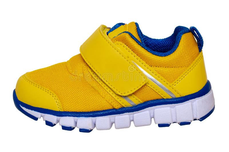 Child shoe fashion. Close-up of one yellow blue child sneaker or sport shoe isolated on a white background. Elegant and trendy. Shoes for girls. Macro stock photography