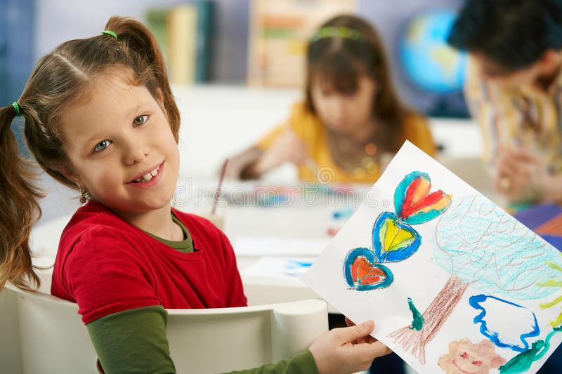 Child showing painting in art class. Portrait of elementary age schoolgirl showing colorful paining to camera in art class in primary school classroom royalty free stock image