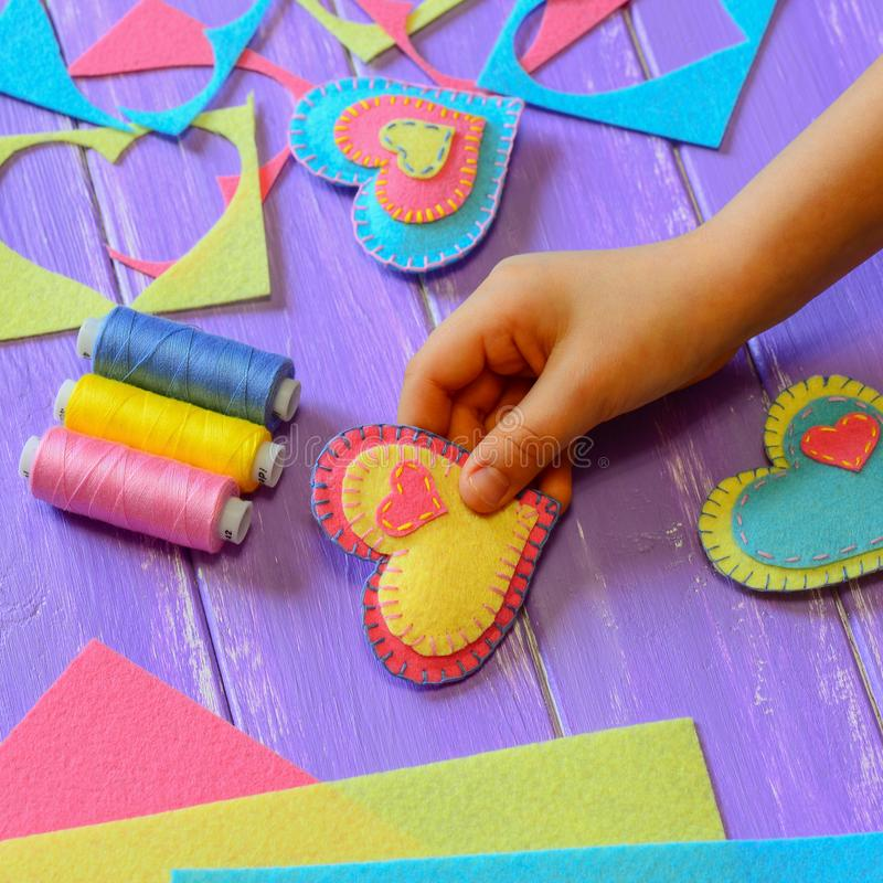 Child shows a felt heart ornament. Kid made a felt heart for Valentines Day. Bright felt hearts, thread set, felt sheets and piece. Valentines Day heart symbol royalty free stock images