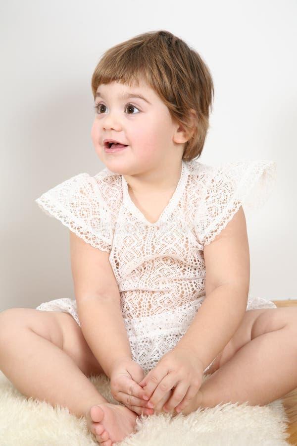 Child sit on fur carpet. The child sit on fur carpet royalty free stock images