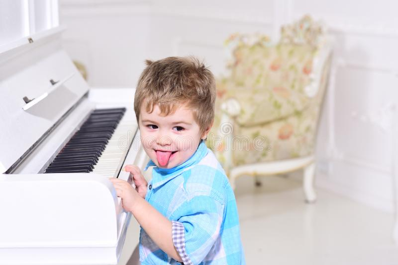 Child sit near piano keyboard, white background. Boy cute and adorable puts finger on keyboard of piano. Elite childhood. Concept. Kid spend leisure near stock images