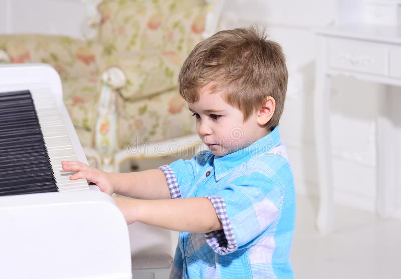Child sit near piano keyboard, white background. Kid spend leisure near musical instrument. Boy cute and adorable puts. Finger on keyboard of piano. Elite stock photography