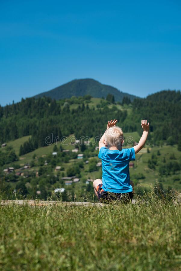 Child sits on mountains background with raised up hands. Weekend in nature with children. Vertical frame royalty free stock image