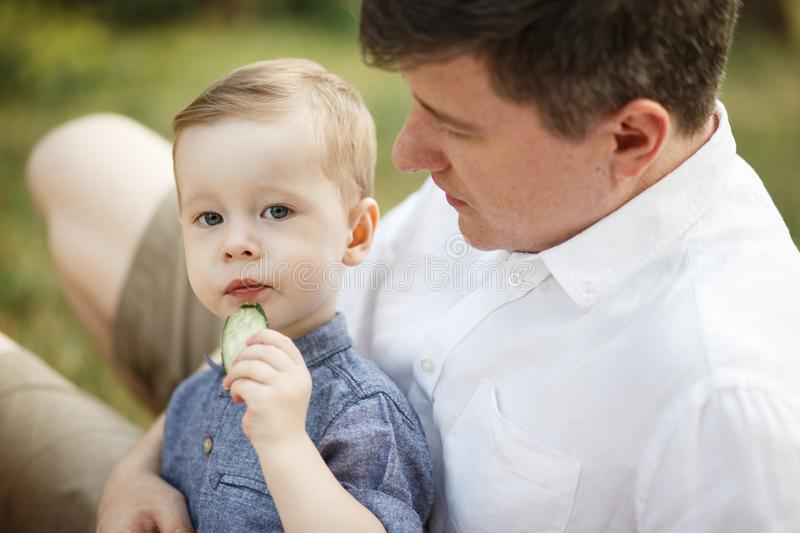 The child sits next to his father in the park. He is eating stock photos
