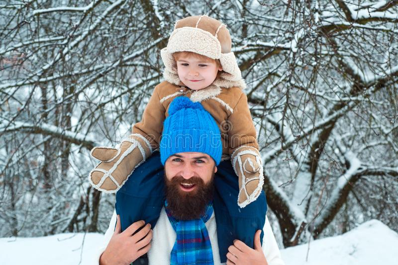 Child sits on the shoulders of his father. Father giving son ride on back in park. Merry Christmas and Happy New Year. Happy child playing with snowball royalty free stock image