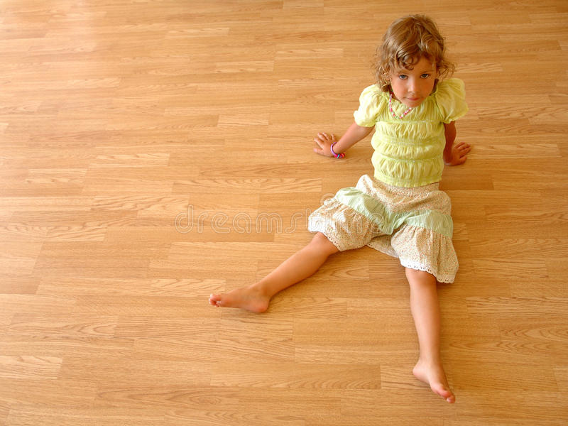 Child sits on wooden floor stock photo