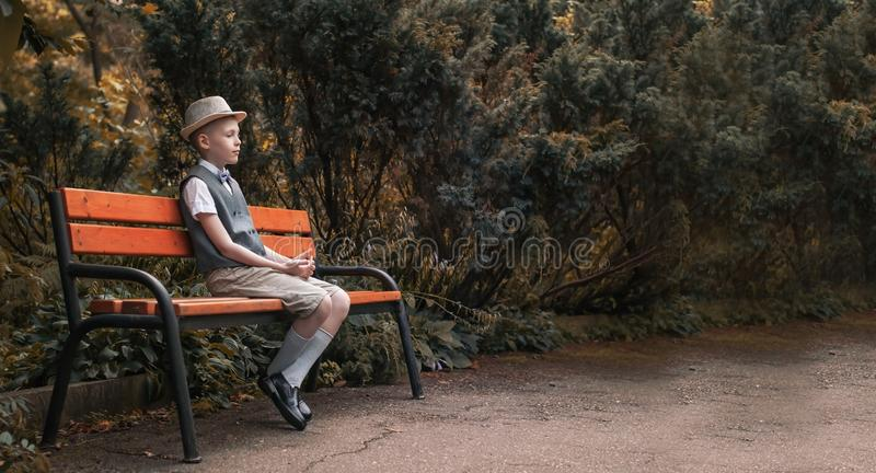 Child sitting at  the bench in a fall park royalty free stock images