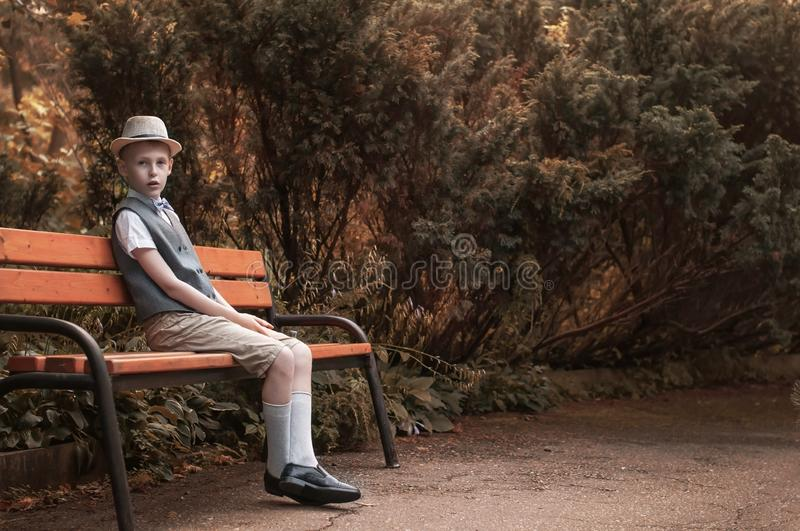 Child sitting at  the bench in a fall park royalty free stock photography