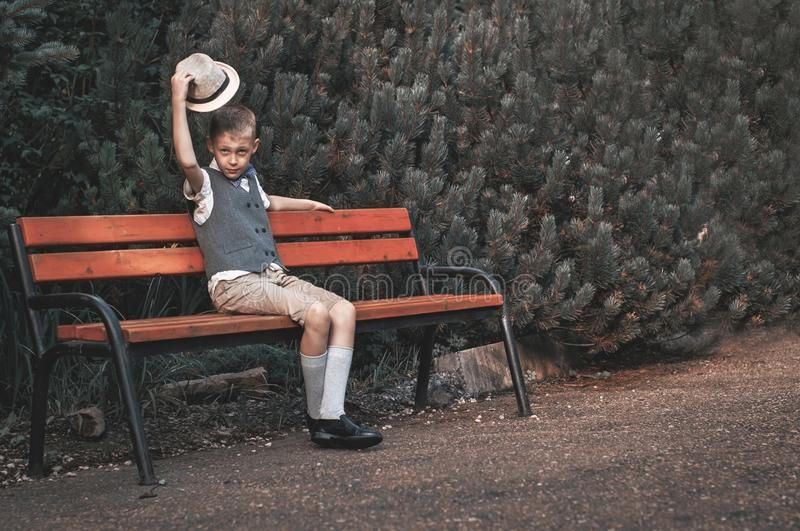 Child sitting at  the bench in a fall park stock photos