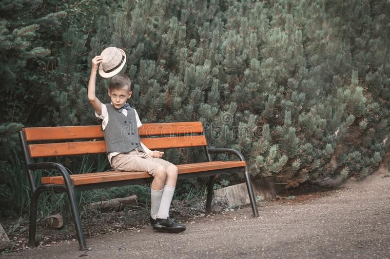 Child sitting at  the bench in a fall park stock photo