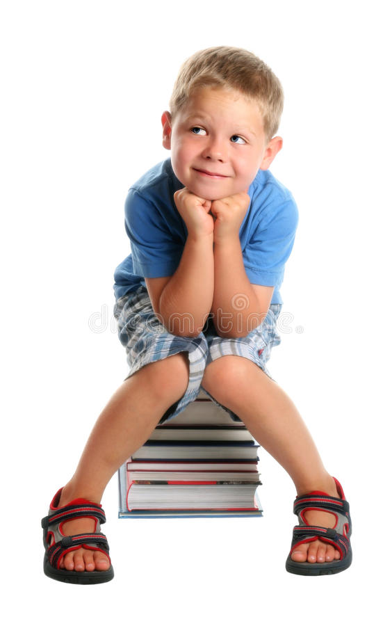 Child sitting on books royalty free stock image
