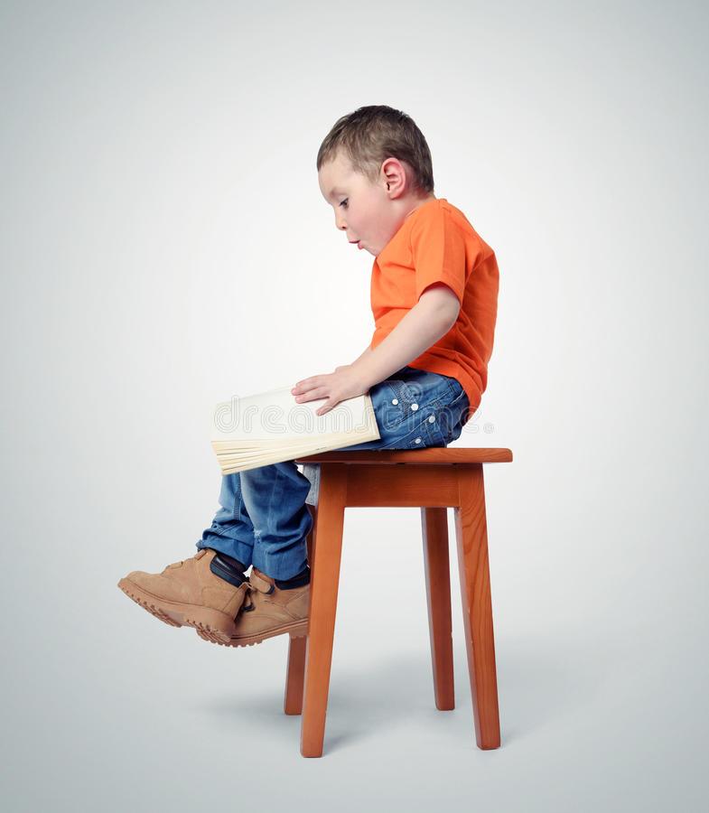 Child sitting on a chair with a book stock images