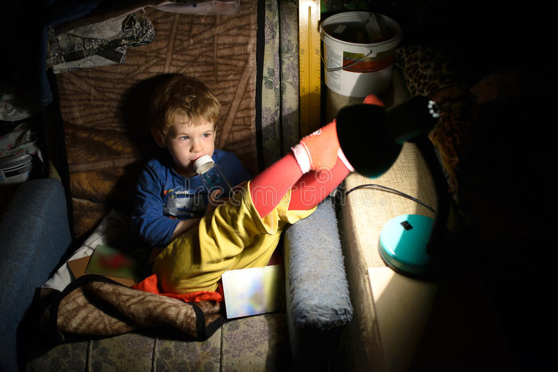 Child Sitting On a Chair In a Dark Room In Front Of The Lamp royalty free stock image
