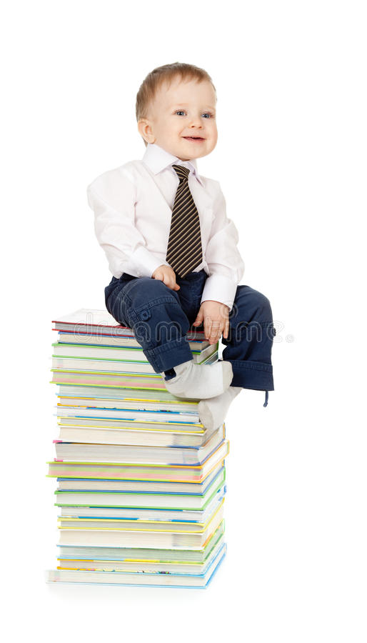 Child sitting on the heap of books royalty free stock photography