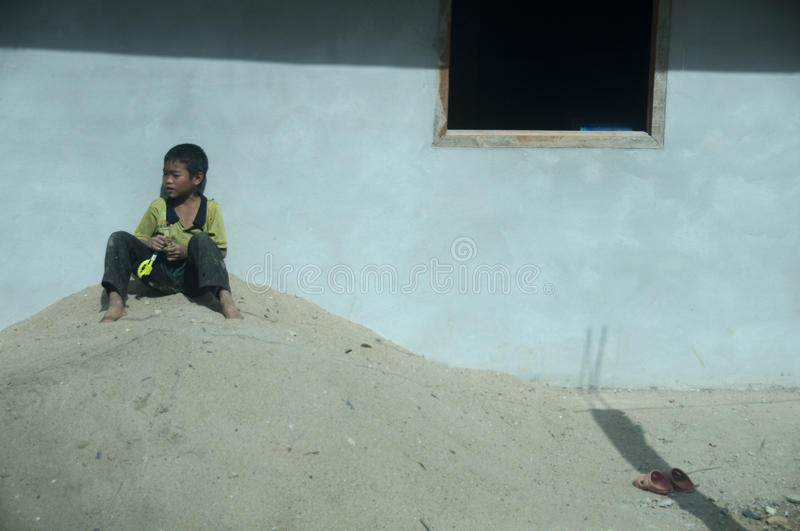 Child sitting outside his house in Laos. royalty free stock photo