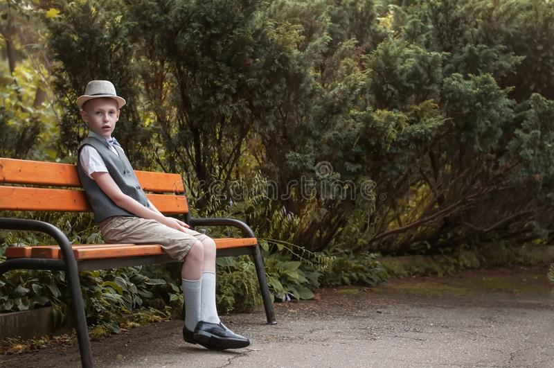 Child sitting at  the park bench in the countryside royalty free stock photos