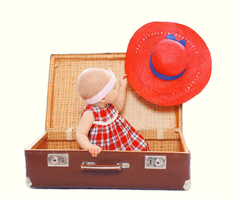 Child sitting in the suitcase with bright red hat royalty free stock photo