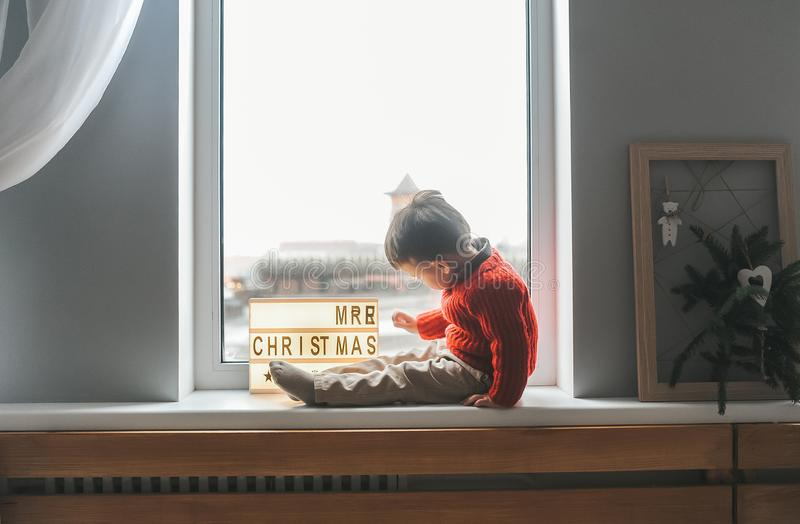 Child sitting on window sill and near Board with the inscription merry Christmas royalty free stock images