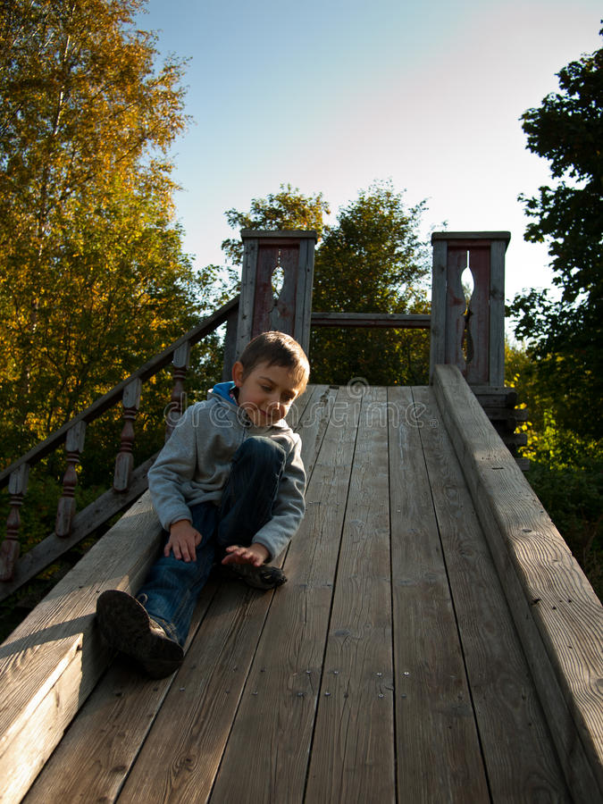 Child sitting on a wooden hill stock photography