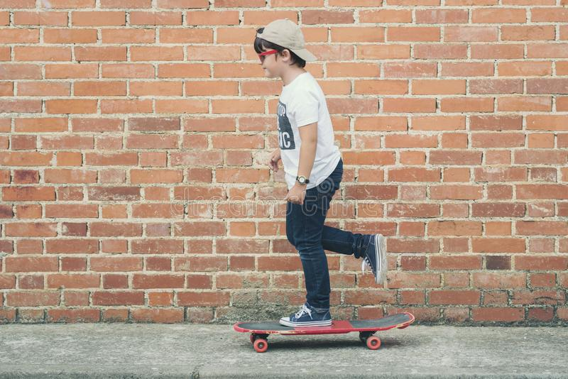 Child with skateboard in the street. Child with a skateboard and sunglasses in the street stock images