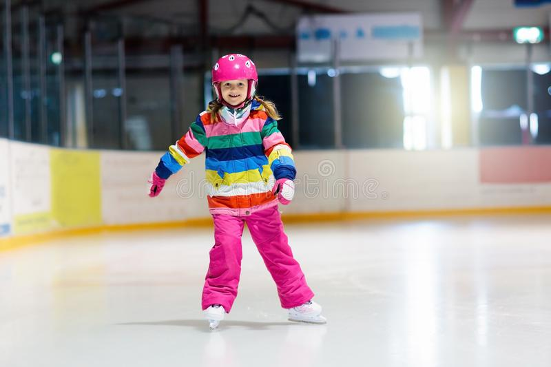 Child skating on indoor ice rink. Kids skate. Active family sport during winter vacation and cold season. Little girl in colorful wear training or learning ice royalty free stock photo