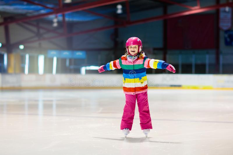 Child skating on indoor ice rink. Kids skate. Active family sport during winter vacation and cold season. Little girl in colorful wear training or learning ice royalty free stock photos