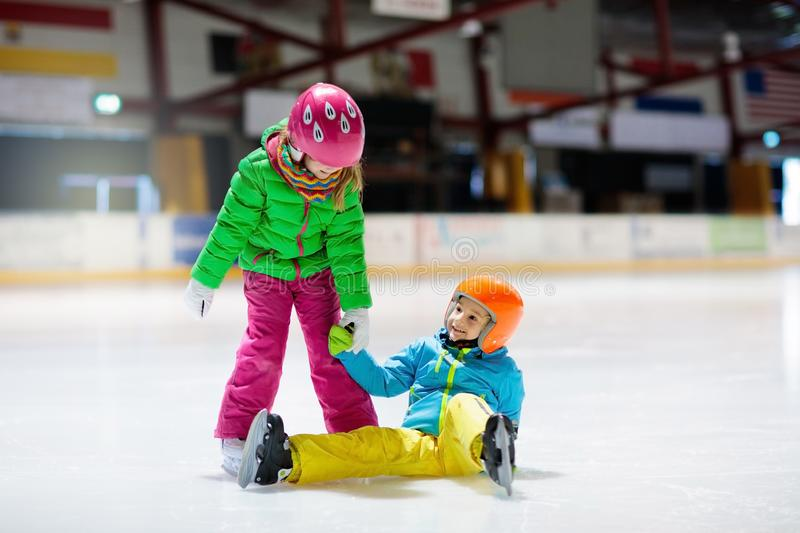 Child skating on indoor ice rink. Kids skate. Active family sport during winter vacation and cold season. Little girl and boy in colorful wear training or stock image