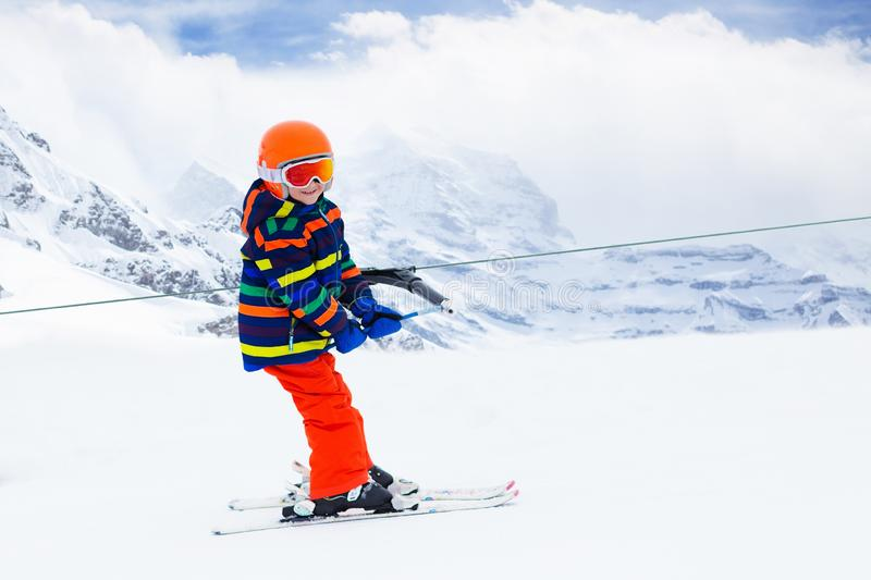 Child on ski lift. Kids skiing. Child on a button ski lift going uphill in the mountains on a sunny snowy day. Kids in winter sport school in alpine resort royalty free stock images