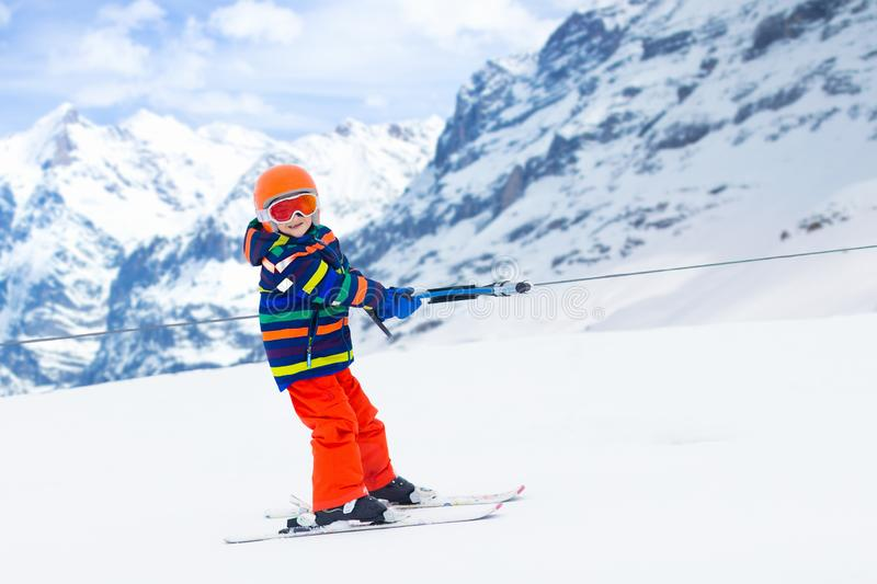 Child on ski lift. Kids skiing. Child on a button ski lift going uphill in the mountains on a sunny snowy day. Kids in winter sport school in alpine resort stock photo