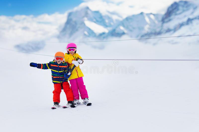 Child on ski lift. Kids skiing. Child on a button ski lift going uphill in the mountains on a sunny snowy day. Kids in winter sport school in alpine resort stock images