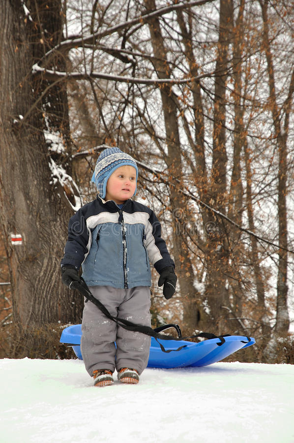Child with sled. Preparing for riding down royalty free stock photo