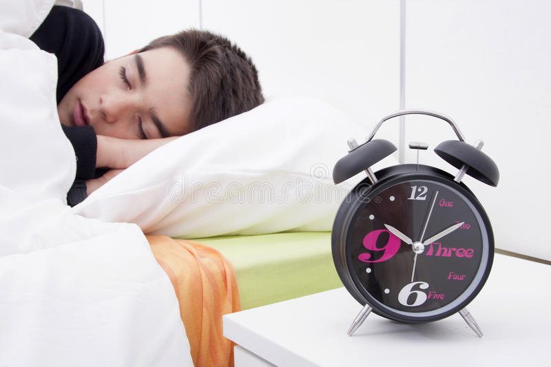 Child sleeping in bed. Alarm clock in the foreground of the room with the child sleeping in bed stock images