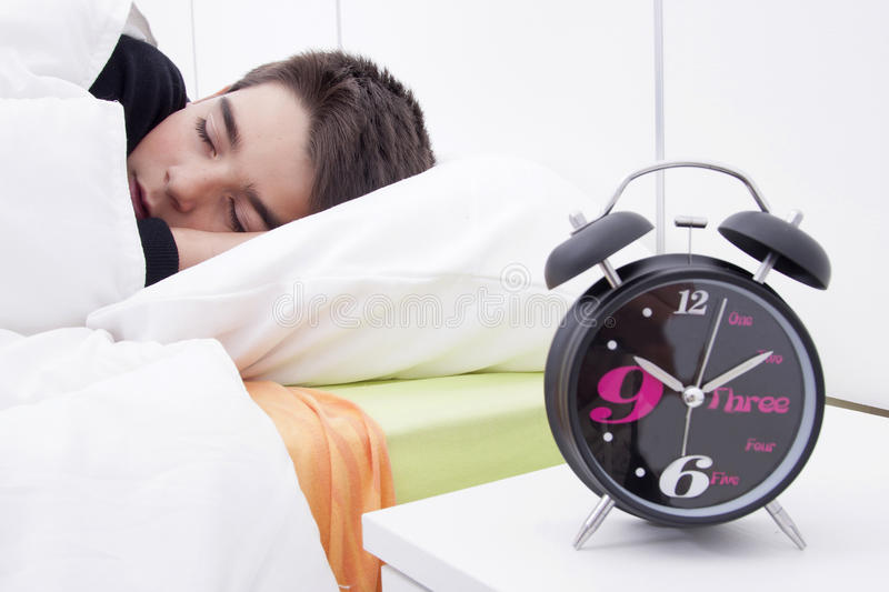 Child sleeping in bed. Alarm clock in the foreground of the room with the child sleeping in bed royalty free stock photography