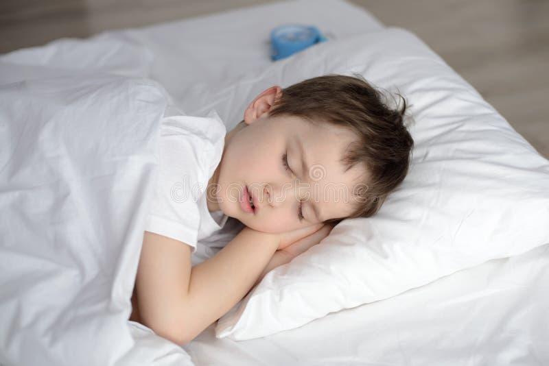 Child sleeping in bed, happy bedtime in white bedroom stock image