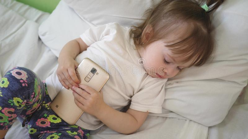 Child is sleeping on pillow and holding a tablet. Cute baby sleeping in bed with smartphone. royalty free stock photography