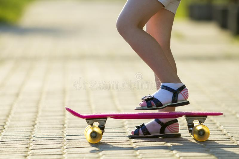 Child slim legs in white socks and black sandals on plastic pink royalty free stock photography