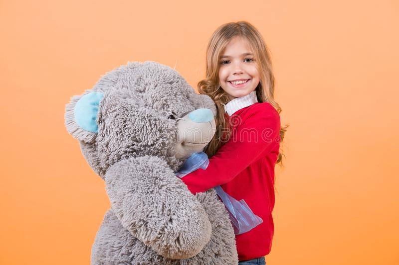Child smile with grey soft toy. Girl hug big teddy bear on orange background. Holiday, birthday, anniversary celebration. Kid with animal doll, present and stock photo