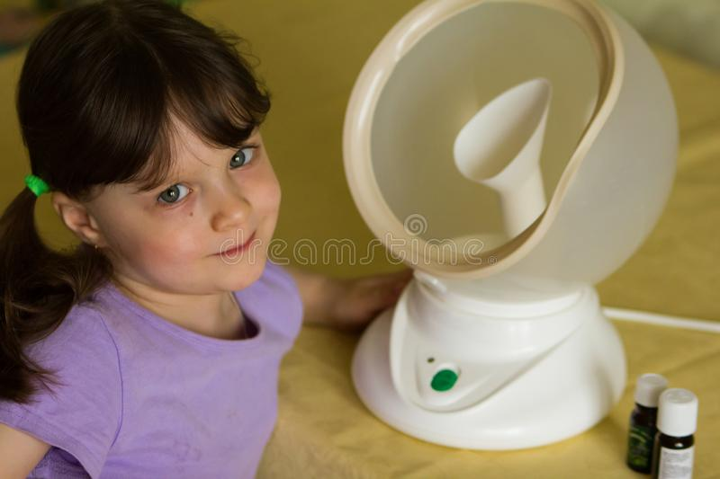 The child smiles next to a round white steam inhaler is treated for flu and cold. On the table are bottles of essential oils and. Medicines. horizontal photo stock image
