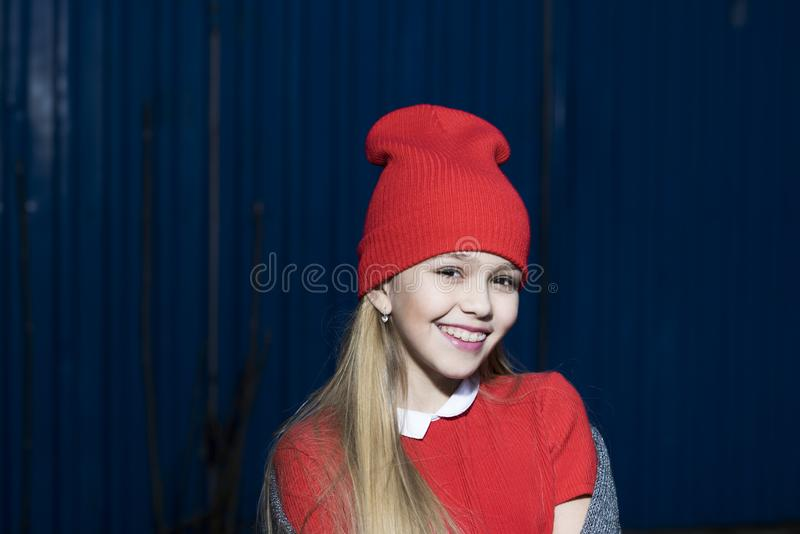 Child smiling with long blond hair outdoor, beauty. Small girl smile in red hat, fashion. Kid fashion trend and style stock photography