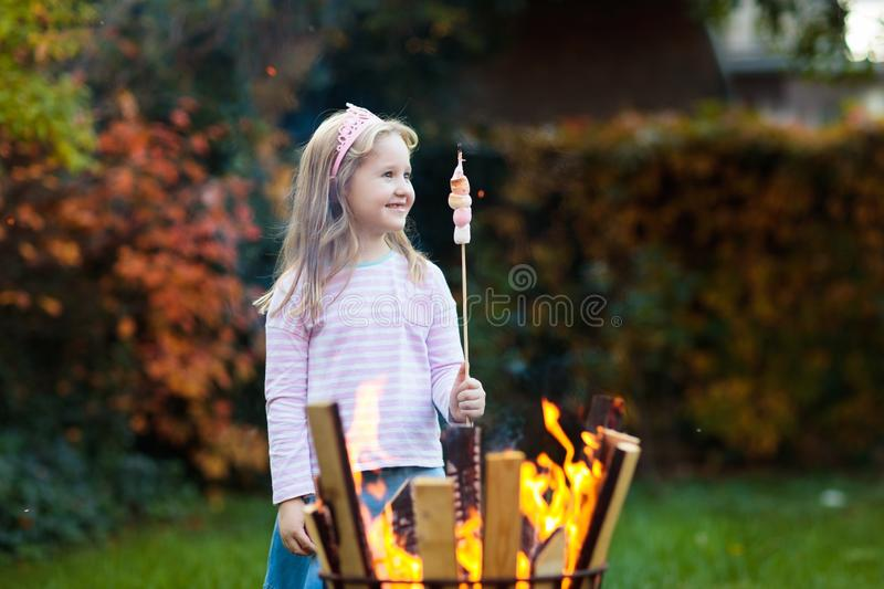 Child with smores at fire. Kids roast marshmallow royalty free stock image