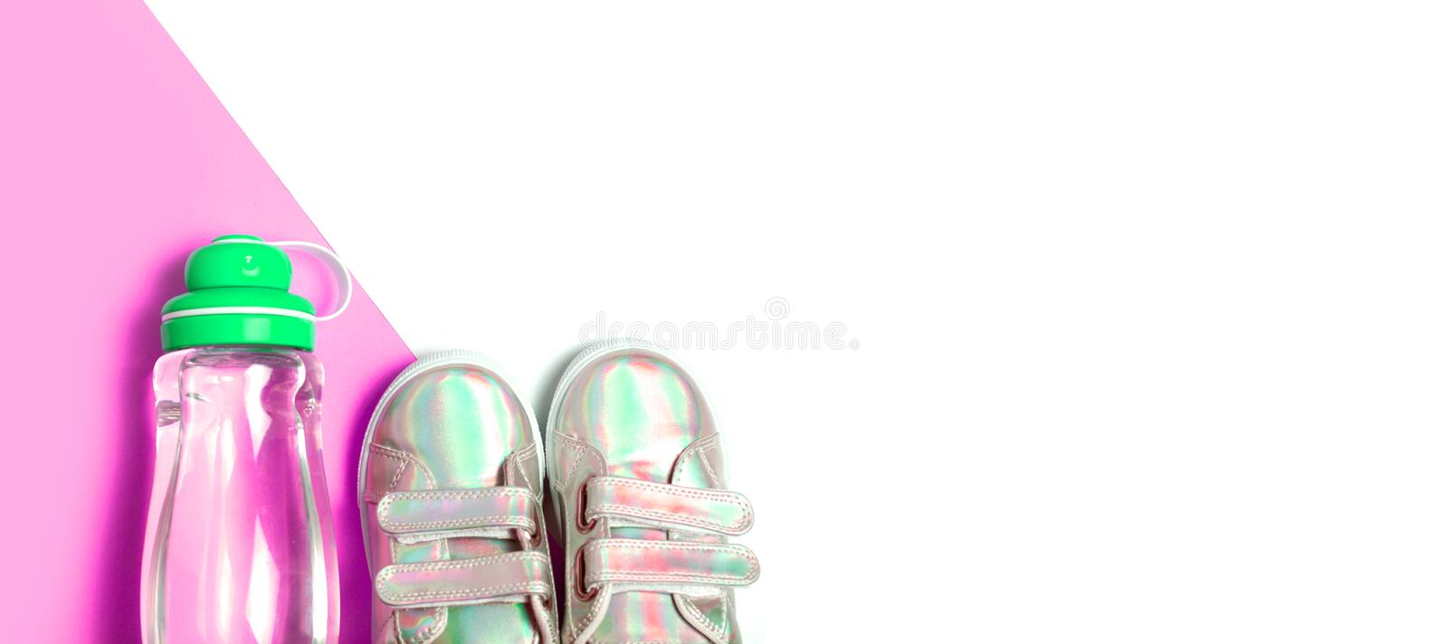 Child sneackers and bottle of water on pink and white background. Top view, flat lay. Copyspace for text. Children healty royalty free stock images