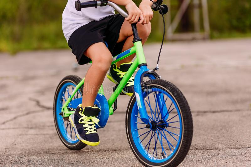 A child in sneakers pedaling a two-Wheeler on the asphalt in the summer. only feet on the pedals of the bike stock photo