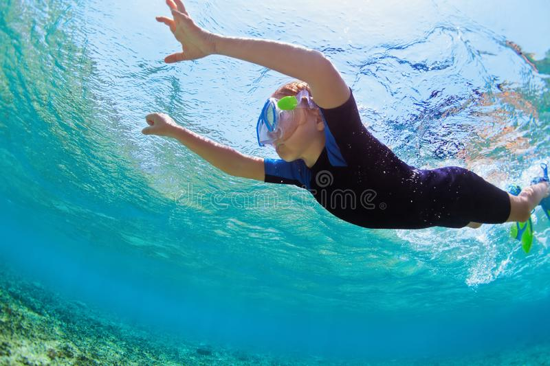 Child in snorkeling mask dive underwater in blue sea lagoon. Happy little kid in snorkeling mask dive underwater with tropical fishes in coral reef sea lagoon stock photo