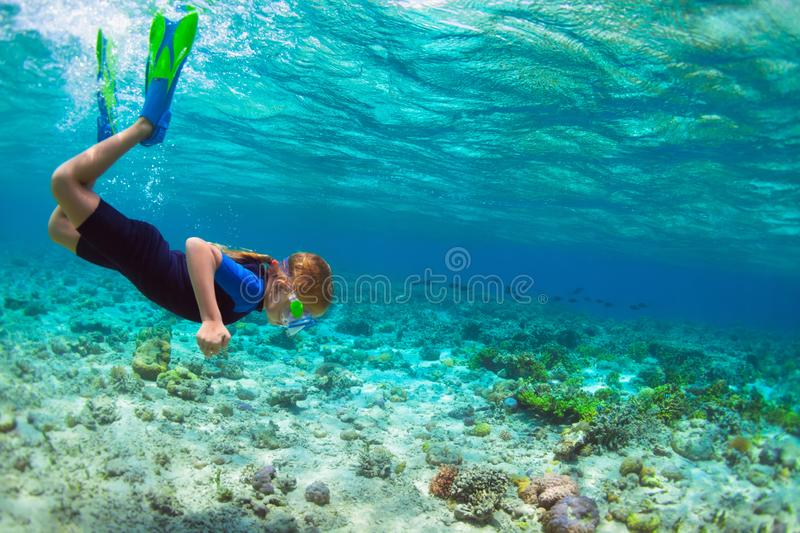 Child in snorkeling mask dive underwater in blue sea lagoon. Happy little kid in snorkeling mask dive underwater with tropical fishes in coral reef sea lagoon stock photos